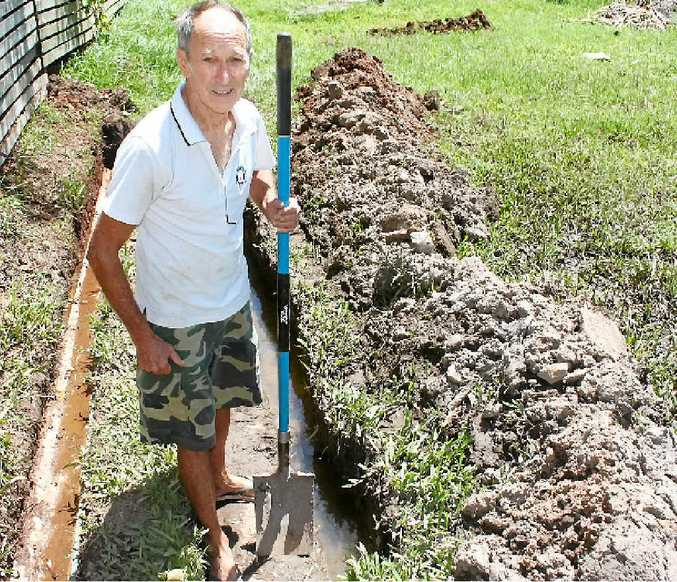 BOGGY SPOT: Ken Harris, 79, takes a much-needed rest after digging this trench to try to access a groundwater pipe on his property. He is fuming with Livingstone Shire Council for its lack of support with cleaning up his property.
