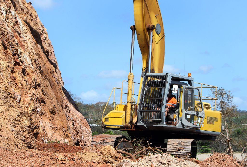A large excavator works to clear lose rock and earth from the cliff adjacent to the Scenic Highway near Statue Bay. Photo: Chris Ison / The Morning Bulletin