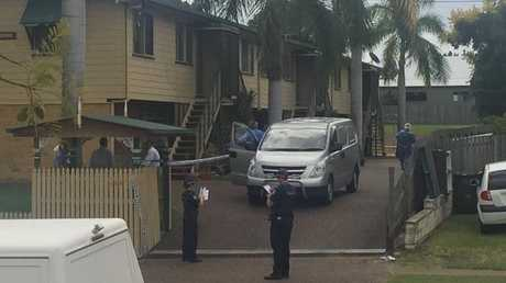 A vehicle parks in the driveway of a unit in Maryborough's Lennox St so police can tranfer the body of a man, who may have died suspiciously, to it.