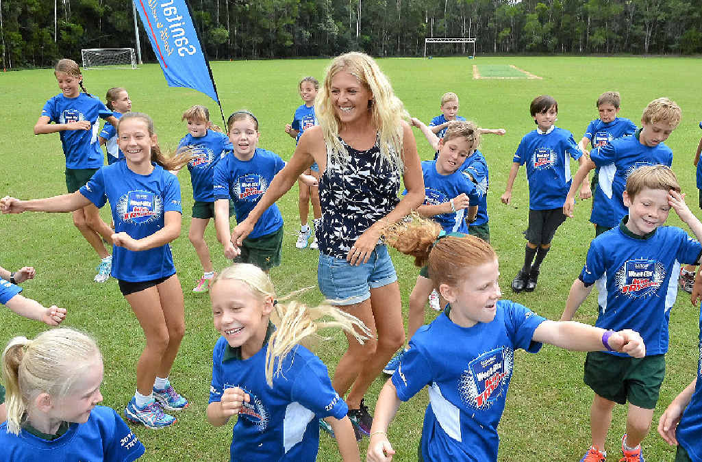 QUEEN OF THE KIDS: Six-time world surfing champion Stephanie Gilmore (above and right) at Sunshine Coast Grammar School yesterday.