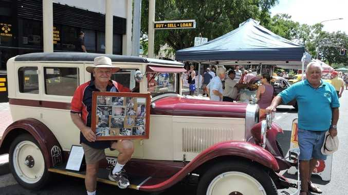 Maryborough District Antique Motor Club members Bill Harris and Lionel Reed display their restored vehicles. Mr Harris holds up photographs of the restoration process of his 1928 Chevrolet sedan.