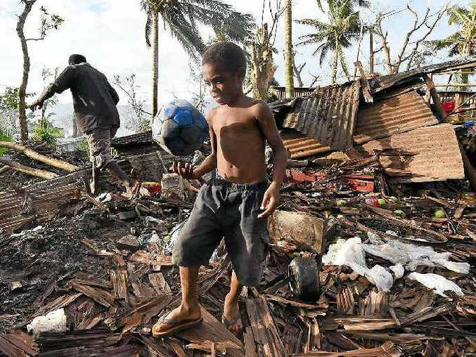 PORT VILLA: A young boy kicks a ball as his father searches through the ruins of their family home in Vanuatu's capital.