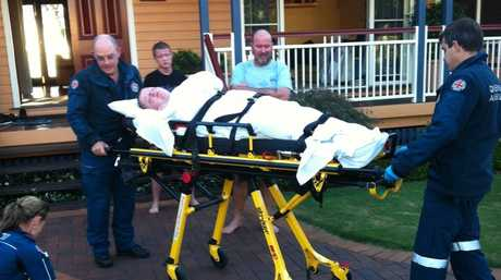 Lachlan Miles is wheeled out on a stretcher by paramedics after one of his many seizures.