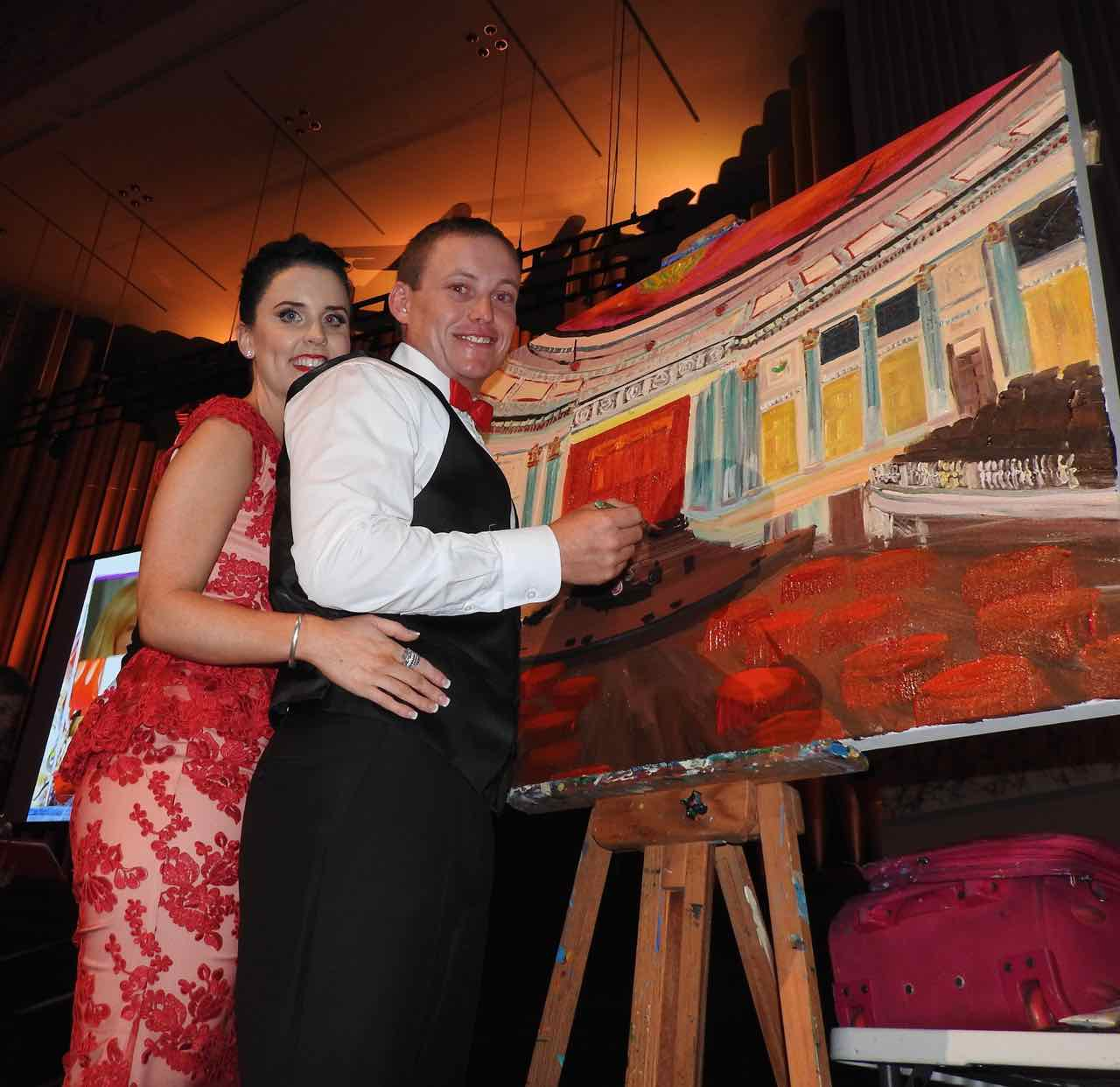 Daniel Morcombe's twin brother Bradley and wife Anna add some touches to a painting which fetched more than $8000 at the 10th annual Dance for Daniel in Brisbane.