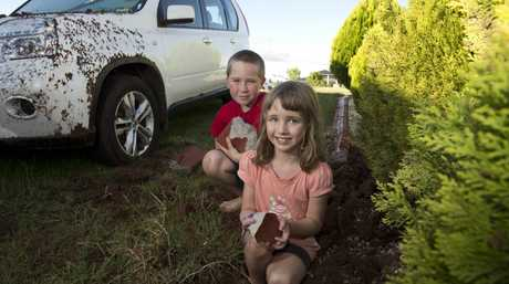 Emily and Michael Congreve hold damaged garden edging blown to bits when lightning hit a flag pole in their front yard.