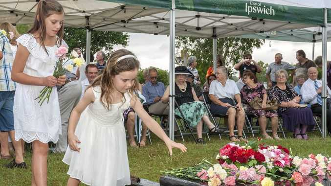 SOLEMN CEREMONY: Rose Robinson and Sophie Griffin lay flowers at the Babies of Walloon grave dedication.