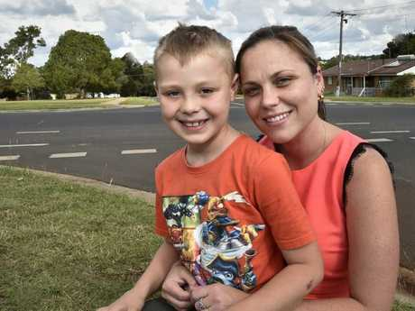 Jordan Bonython, 6, is cuddled by his mother at the Drayton intersection where he was hit by a car while riding a bike.
