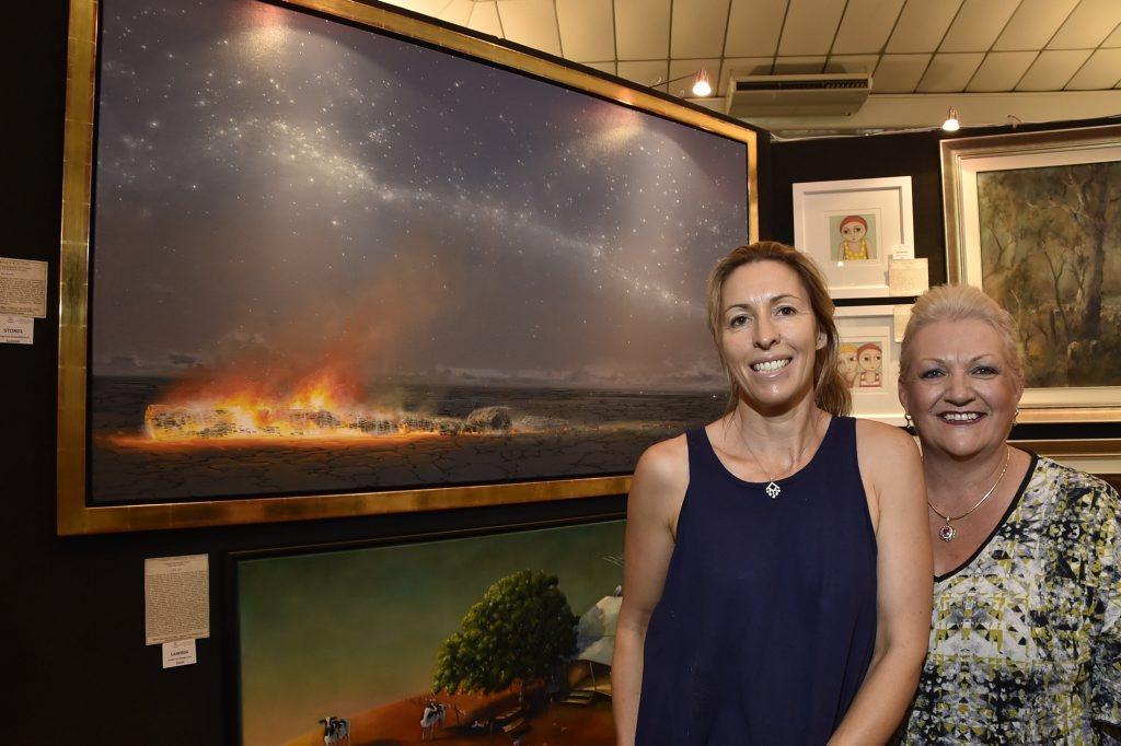 Grammar Art Show committee member Bec Statton and Rowena Hogan admire Tim Storrier's painting.