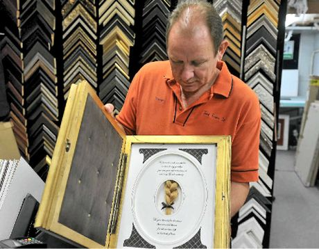 FRAMED: Trevor Yates from Just Frame It has again won an international competition recognising his skills as a professional framer. He holds the winning piece, a tribute to a girl who passed away in the 1900s. The girl's identity remains unknown.