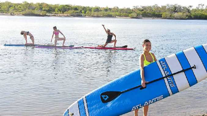 NEXT LEVEL: Trainer and yoga instructor Lisa Burgess with stand-up paddle board participants.