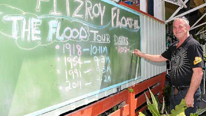 FITZROY FLOATEL: Tony Higgins updates the flood sign outside his Rockhampton hotel in 2012.