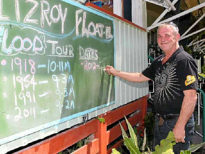 FITZROY FLOATEL: Tony Higgins updates the flood sign outside his Rockhampton hotel in 2012.