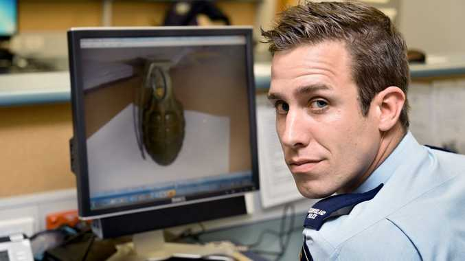 Constable Jordan Powell with a picture of the live grenade surrendered at the Hervey Bay police station.