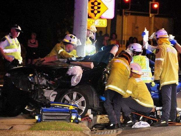 Emergency services work to cut a man out of his car after it crashed on Chapman Dr, Gladstone on Monday night.
