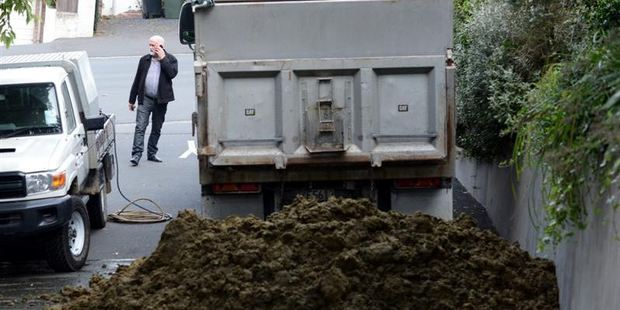 Contractors prepare to clean up excrement dumped outside the Otago Regional Council's Dunedin office by a disgruntled North Otago farming couple.