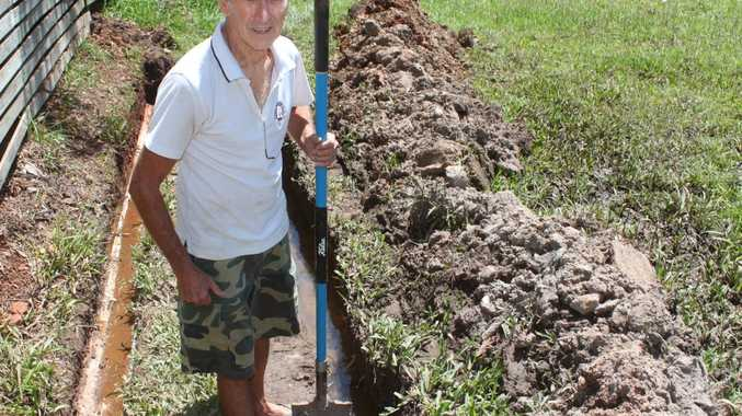 Ken Harris, 79, takes a much needed rest after digging this trench to try to access a groundwater pipe on his property. He is fuming with Livingstone Shire Council for their lack of support with cleaning up his property. Photo Austin King / The Morning Bulletin