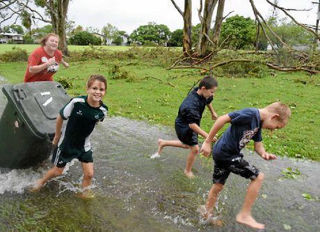 LEFT: Kids in Berserker play in the water left by Cyclone Marcia. Lisa Benoit