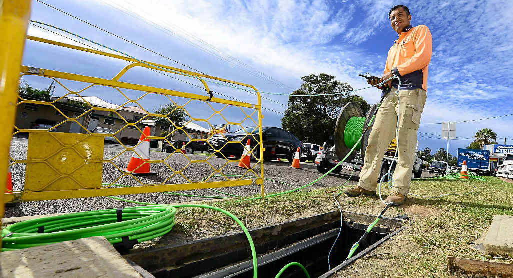 PLENTY OF WORK AHEAD: An NBN employee lays down fibre optic cable.