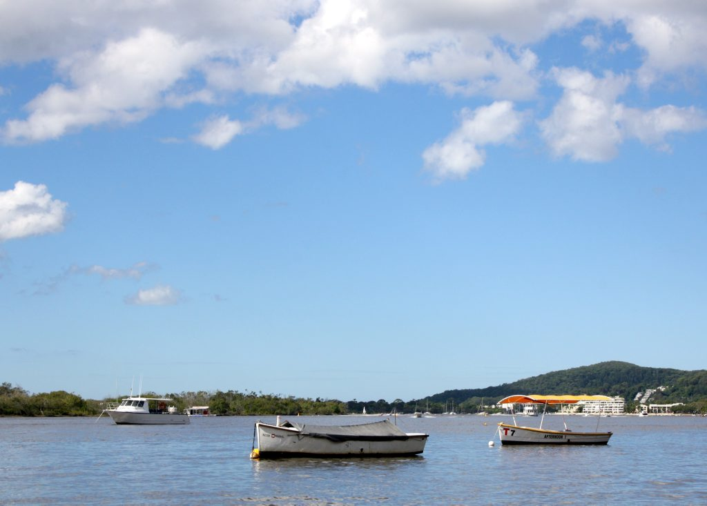 Boats swing at their moorings on Noosa River at Noosaville.
