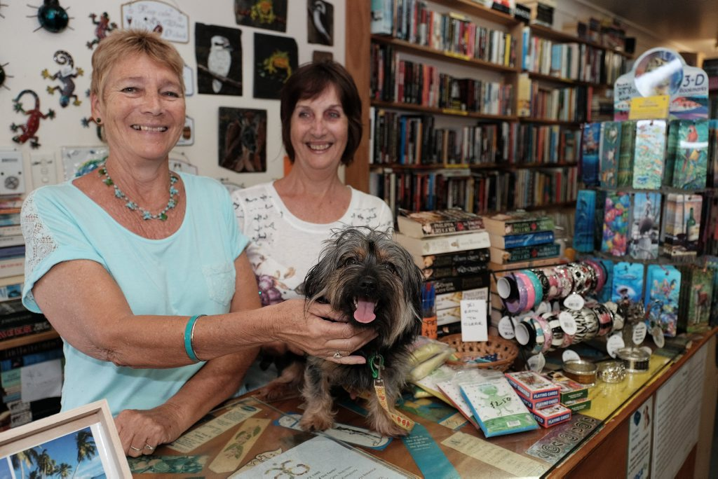 GRAND ADVENTURE: 'Bundy' the Yorkshire Terrier with Lea's Book Exchange owner Lea Payne and assistant Wendy Galloway. 'Bundy' hitch-hiked her way from Bundaberg to Airlie Beach, where she was dropped off by a group of German backpackers at the book store. Photo Matthew Newton / The Guardian