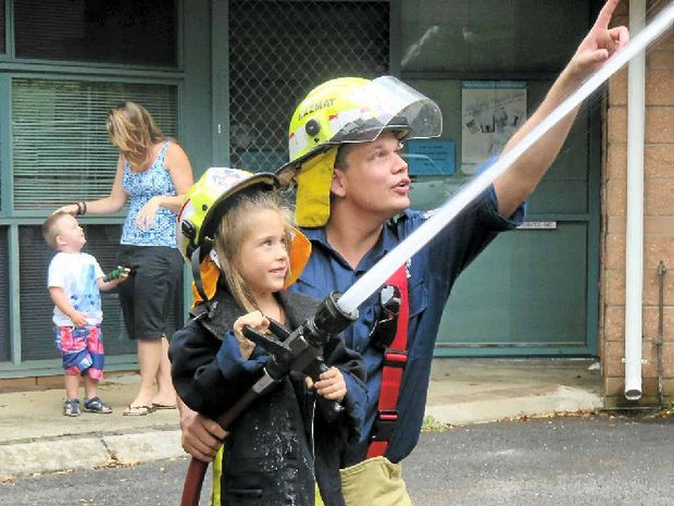 A pre-schooler feels the power of the fire hose used to extinguish blazes in the Lismore and Goonellabah areas.