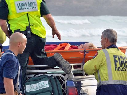 Emergency services load a boy onto the back of a four wheel drive vehicle after he was injured in a light plane that flipped while making a forced landing on Tomahawk Beach.