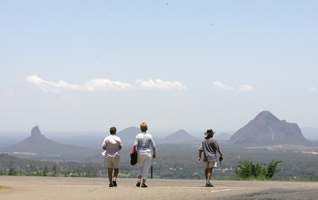 Visitors to Mary Cairncross Park look through the heat haze towards the Glasshouse Mountains from the road.