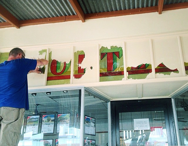 Nathan Ranft scrapes away old paint revealing the beauty of the old Loetzschs Bike Store sign. Photo: Lois Kilmartin