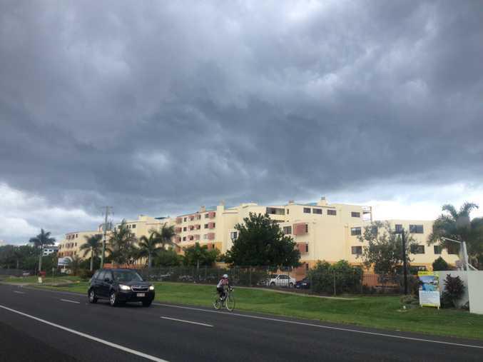 Rain clouds loom over cyclist at Marcoola