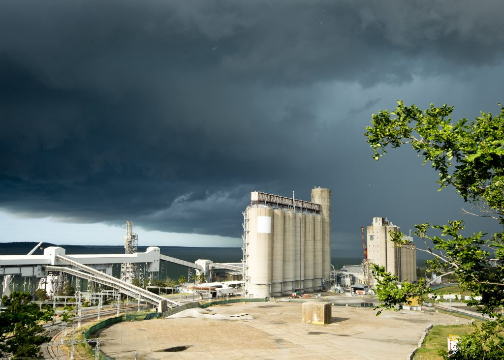 A storm front crosses the Gladstone region, with dark clouds rolling in from the south.