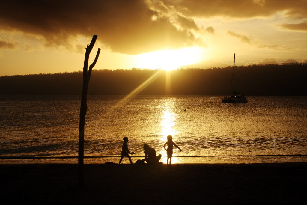 The sun glistens on the water as children play carelessly. Vanuatu aftermath from Cyclone Pam. Photo Vicki Wood / Caboolture News