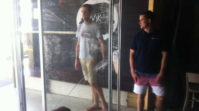 Nook & Cranny owner Cameron Scott (right) tells a customer his Nambour bar is closed after thieves broke in a stole a safe.