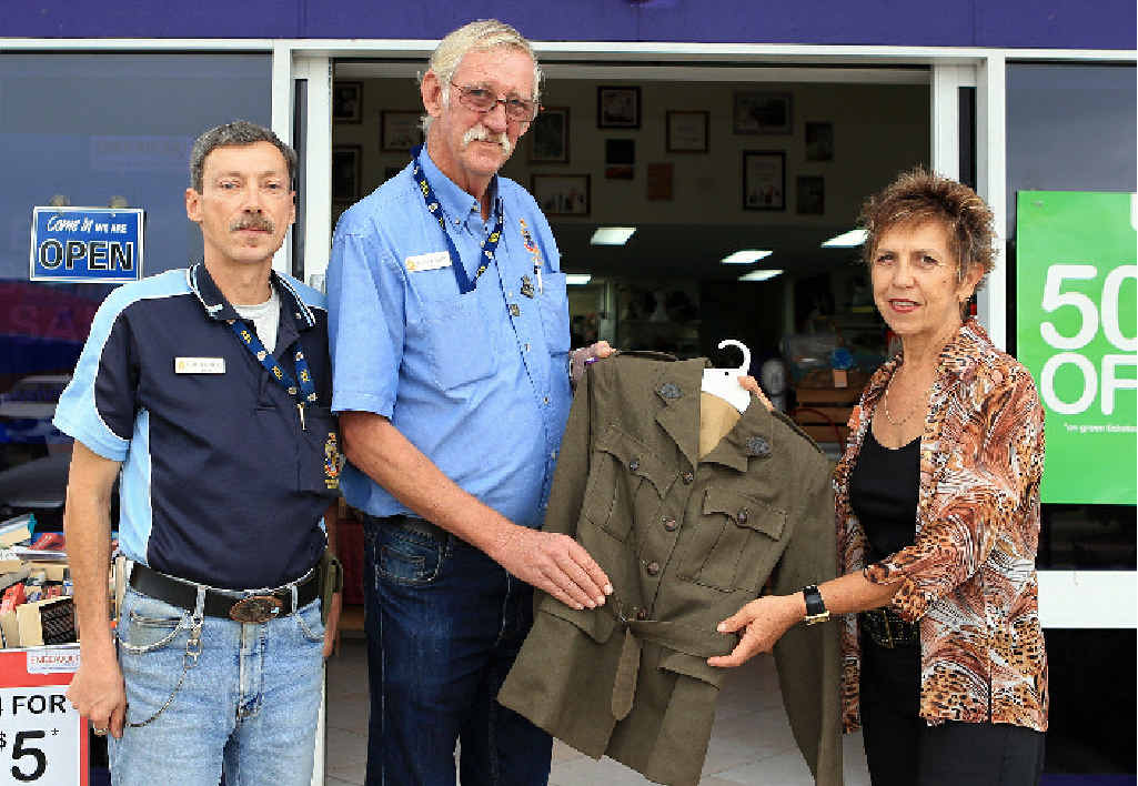 Simon Morley (left) and John Kelsey from the Hervey Bay RSL Sub Branch, receiving a World War Two Australian women's army service uniform from Chris Spink of the Endeavour Foundation.