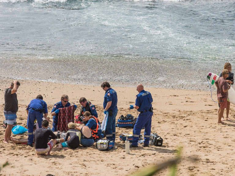 Paramedics from NSW Ambulance and Westpac Rescue Helicopter stabilise a man on Angourie Point beach after he was brought in after a suspected heart attack while surfing.