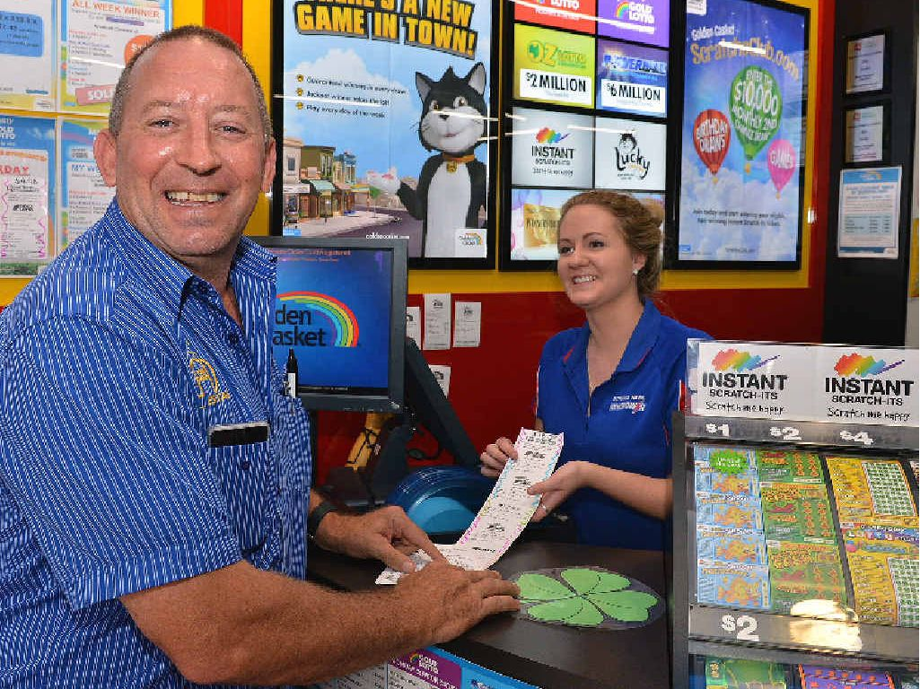FINGERS CROSSED: Greg Gilmore from Tom Grady Real Estate buying his Lotto tickets from Nicki Wilcox at Patrick's Casket and Newsagency, Mary St, Gympie.