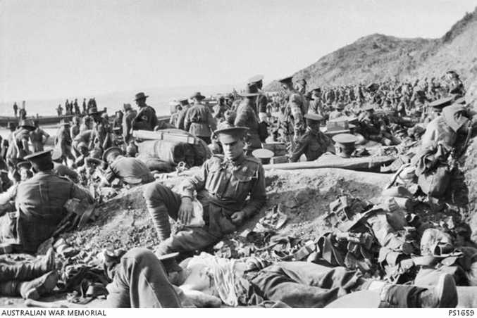 An Australian soldier lies wounded in the foreground, as hundreds of other soldiers move among the dead and wounded on the beach at Anzac Cove on the day of the landing. The soldiers wearing Red Cross arm bands are tending to the wounded.