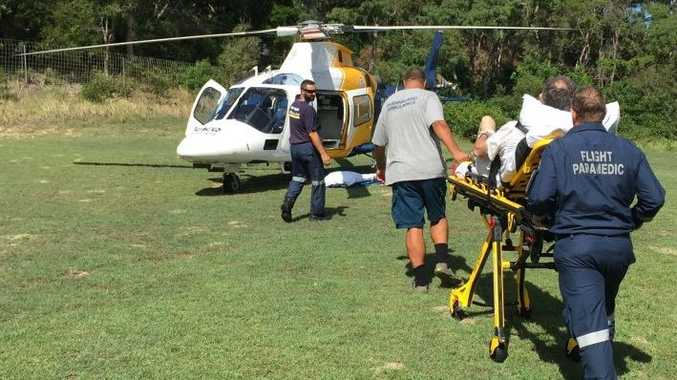A Scottish tourist is wheeled to the RACQ Careflight Rescue helicopter after suffering a fall on Fraser Island.