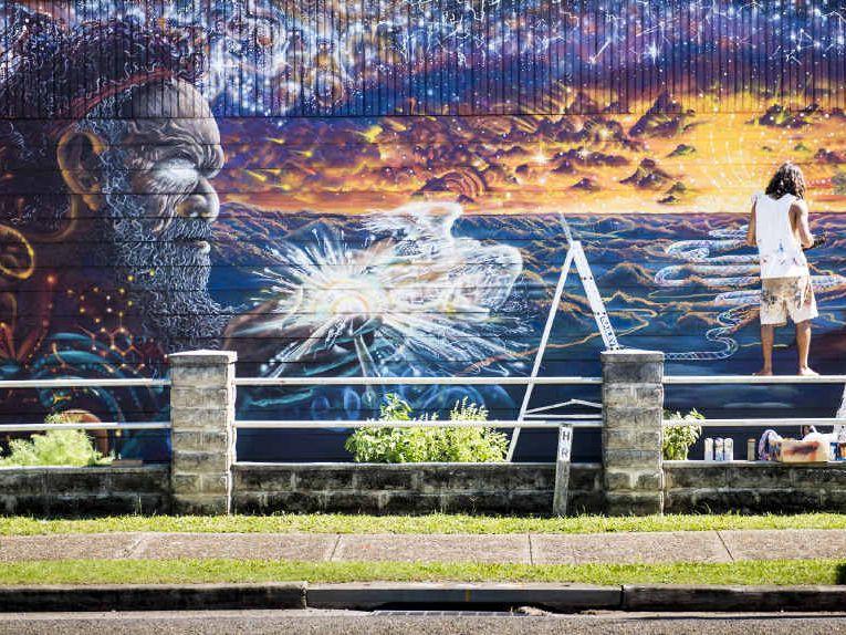 BREATH OF LIFE: Byron Bay artist Gene Cundith works on a spectacular mural at Ulmarra.