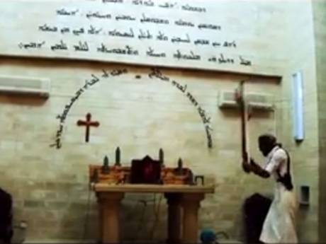 An Isis militant smashes a cross on an altar