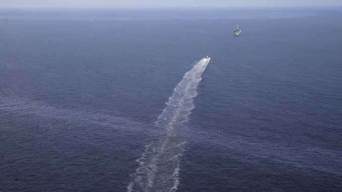In this March 31, 2015 photo, the wake of a supply vessel heading towards a working platform crosses over an oil sheen drifting from the site of the former Taylor Energy oil rig in the Gulf of Mexico, off the coast of Louisiana