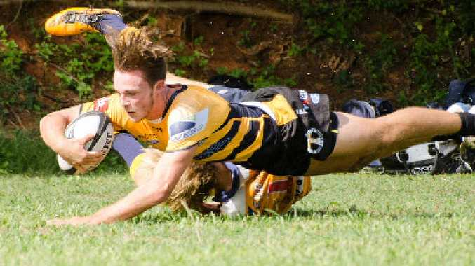 TRY TIME: Caloundra's T. Rogers dives over Kyle Johnstone in the match against the Hammers.