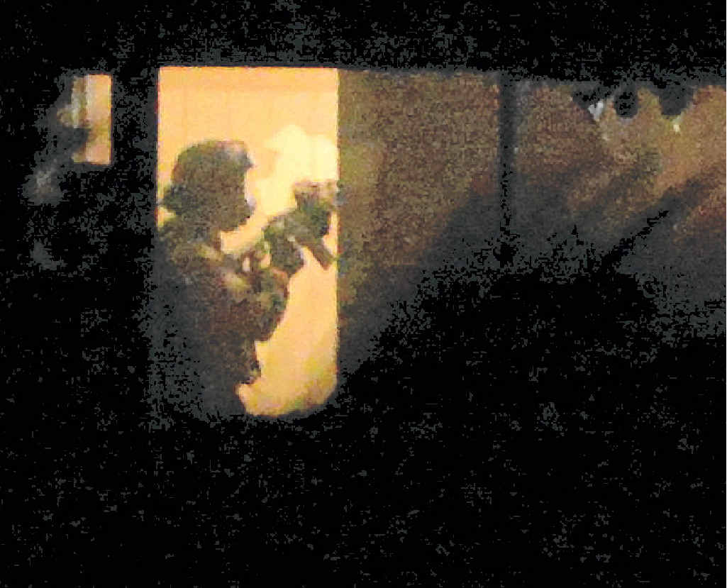 ENTRY: Police armed with military style weapons enter the house at the peak of Tuesday night's drama