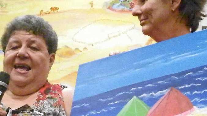 UNDER HAMMER: Wendy Lutvey (left) speaks about her beach scene at Gayndah Art Gallery's 2013 Art Attack auction.