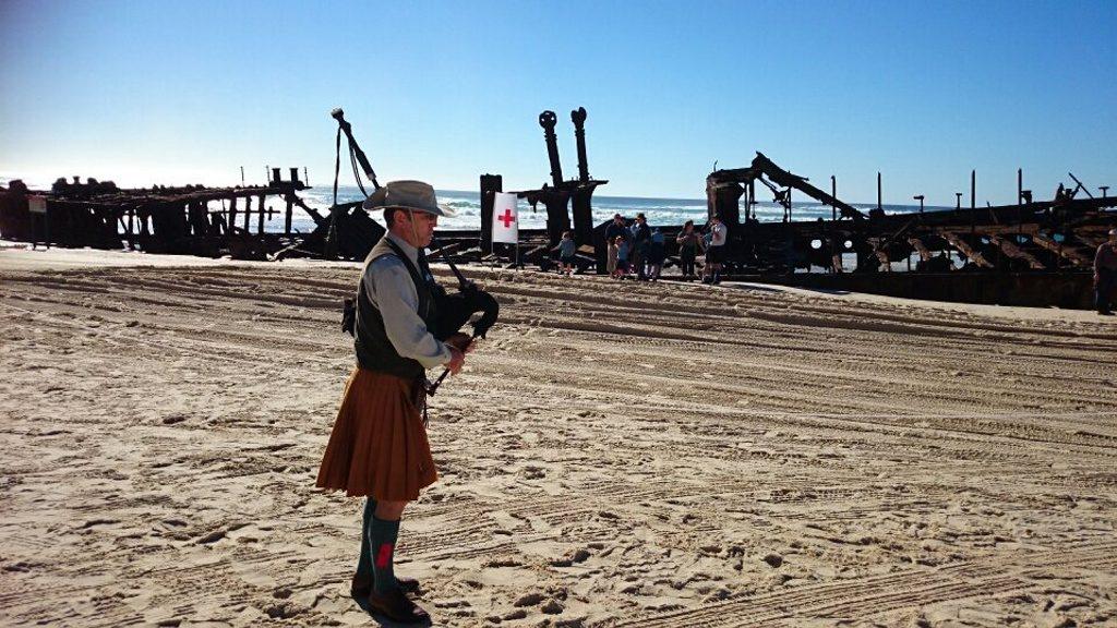 Frank Ekin plays the bagpipes as the waves crash over the Maheno shipwreck.