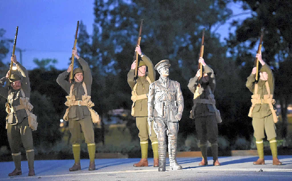 Members of the 9th Battalion AIF Living History Unit fire a salute behind the statue.