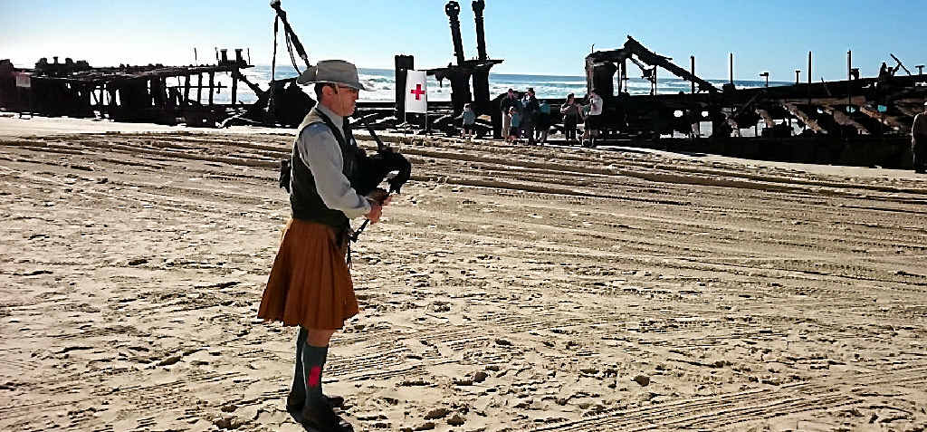 PAYING TRIBUTE: Frank Ekin plays the bagpipes as the waves crash over the wreck of the Maheno.