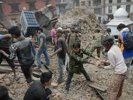 People clear rubble in Kathmandu's Durbar Square, a UNESCO World Heritage Site that was severely damaged by an earthquake on April 25, 2015.