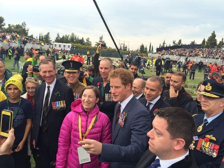 Prince Harry poses with crowd members before the Lone Pine Australian service.