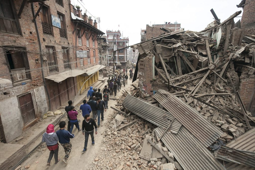 epa04721379 Local residents in search of safe accommodation walk along a narrow road past a massively destroyed building 26 April 2015 - twenty four hours after a devastating earthquake that so far has taken the lives of more than 2,400 people. EPA/Hemanta Shrestha
