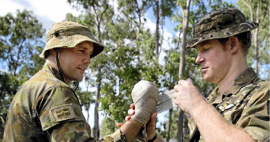 ROYAL TREATMENT: His Royal Highness Prince Henry of Wales applies a bandage to Lieutenant Gerard Hinchliffe during an exercise at the Royal Australian Artillery in Darwin's Robertson Barracks.